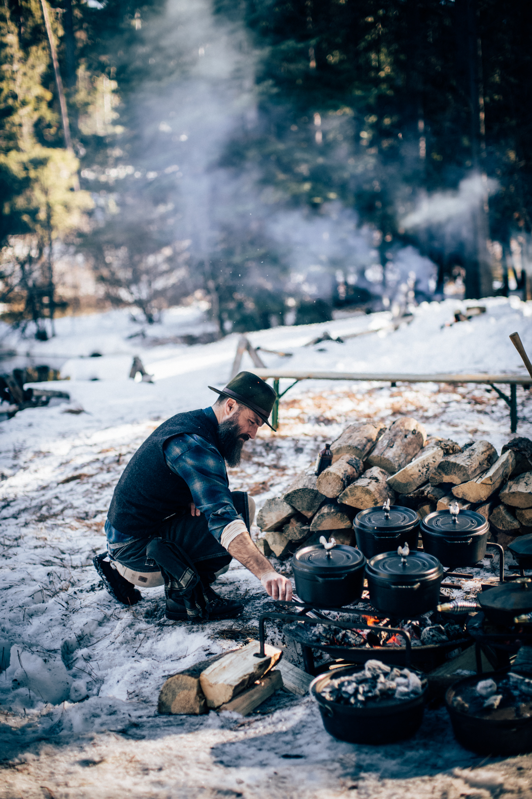 Rugged man cooking over a fire in snow - Top 5 Cozy Camp Site Dinner Scenes - La Mesa RV